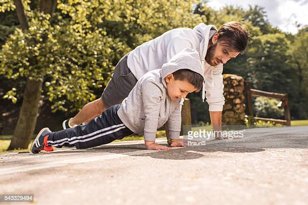 Father and son exercising push-ups in the park.