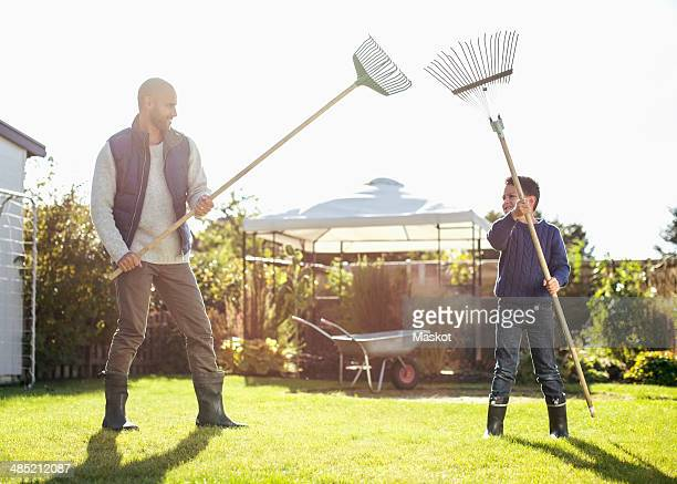 Father and son fighting with rakes at yard