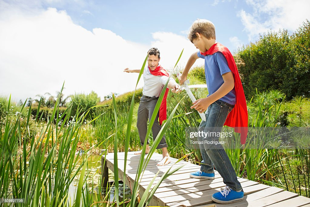 Father and son (6-7) fighting with wooden swords on pier : Bildbanksbilder