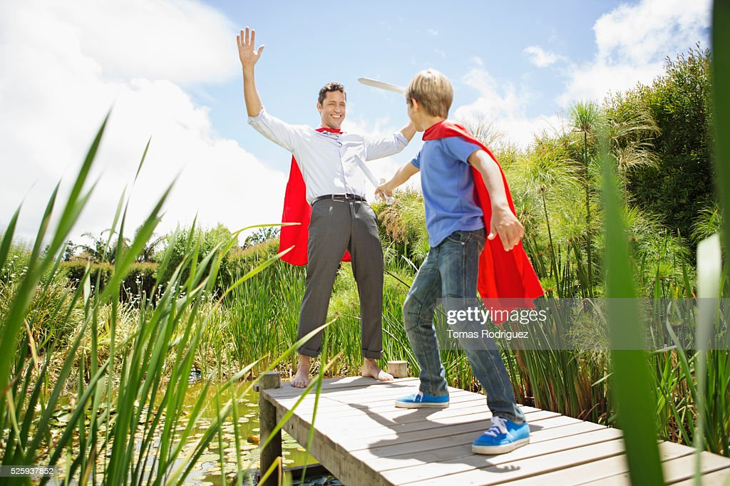 Father and son (6-7) fighting with wooden swords on pier : Foto de stock