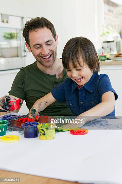 father and son finger painting together - finger painting stock pictures, royalty-free photos & images