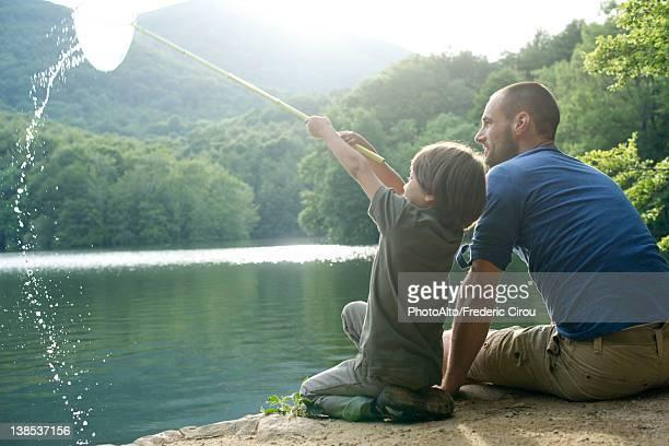 father and son fishing, boy holding up fishing net - familia con un hijo fotografías e imágenes de stock