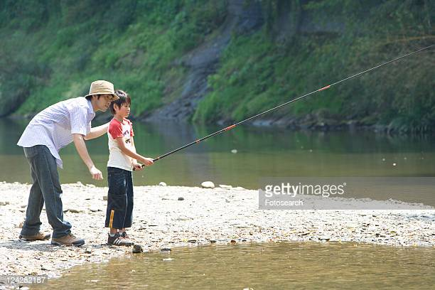 Father and Son Fishing by Stream