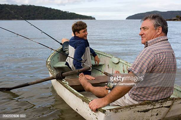 Father and son (12-14) fishing from boat, boy looking over shoulder
