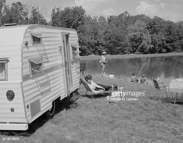 """"""" father and son fishing in river, girl sitting with mother and listening tape recorder"""" - {{ contactusnotification.cta }} stockfoto's en -beelden"""