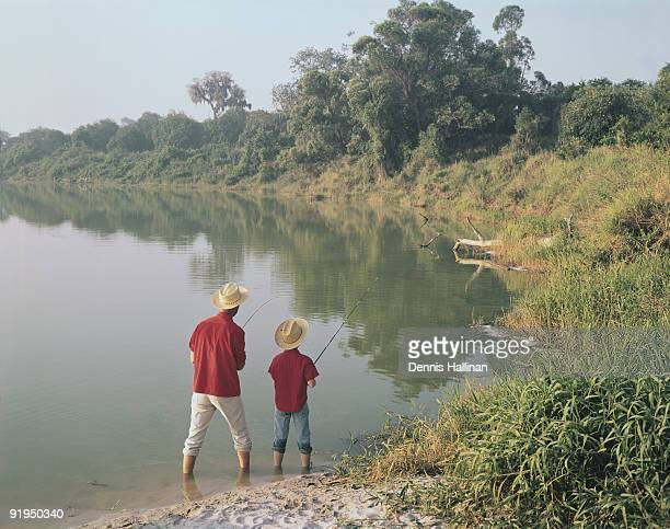 Father and son fishing in shallow lake
