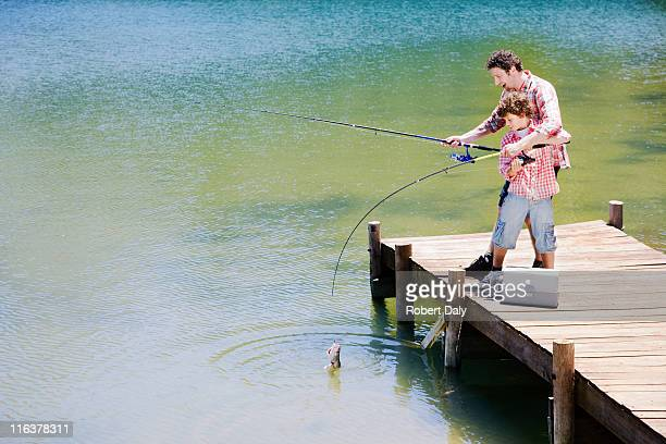 father and son fishing off dock - one animal stock pictures, royalty-free photos & images