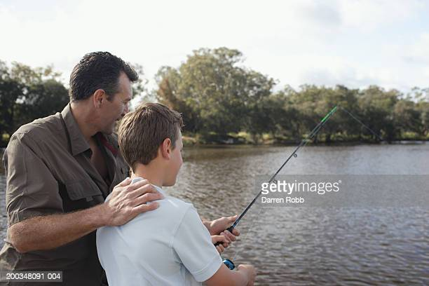 Father and son (10-12) fishing off jetty, rear view