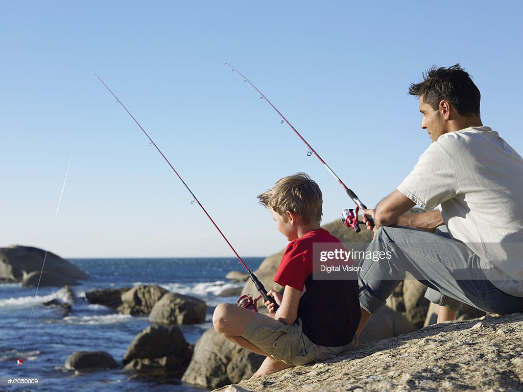 Father and Son Fishing on a Rock : Stock Photo