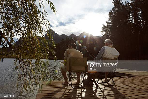 father and son fishing on jetty - fishing stock pictures, royalty-free photos & images