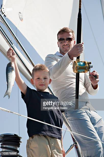 father and son fishing on yacht - catching stock pictures, royalty-free photos & images