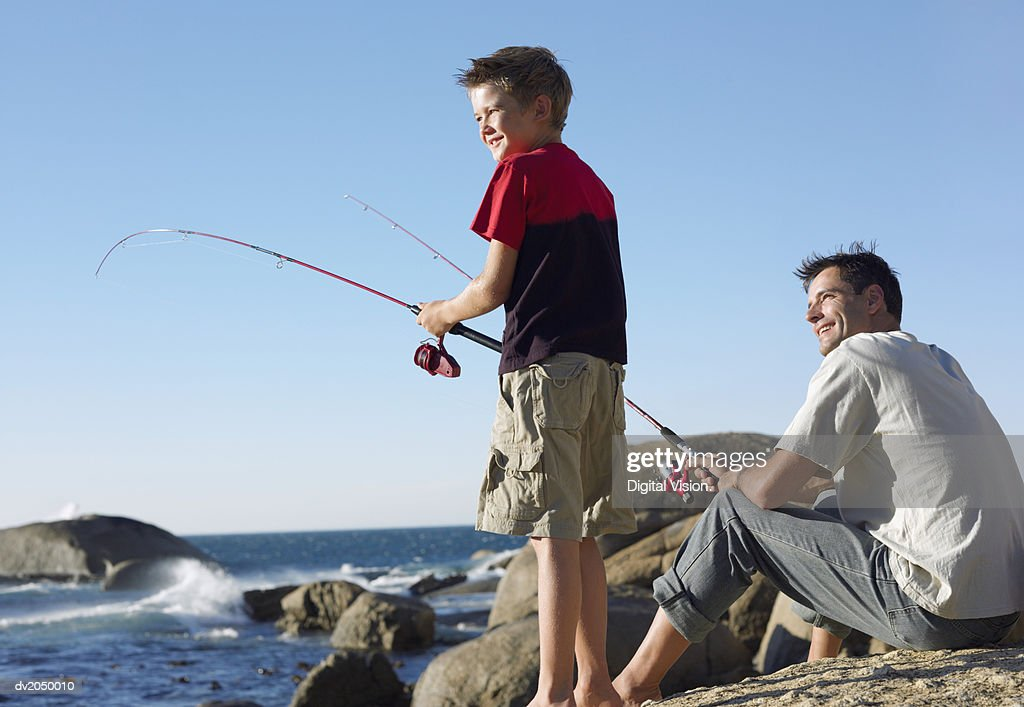 Father and Son Fishing Together on a Rock : Stock Photo
