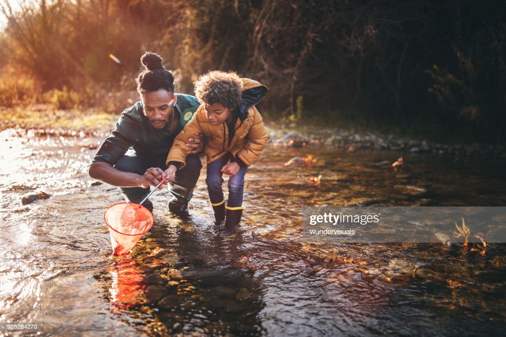Father and son fishing with fishing net in river : Stock Photo