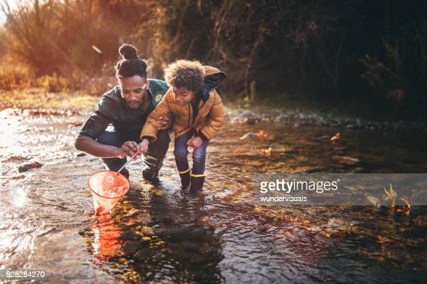 father and son fishing with fishing net in river - sunset lake stock photos and pictures