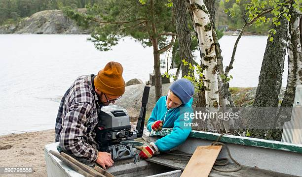 father and son fixing the engine before launching the boat. - watervaartuig stockfoto's en -beelden
