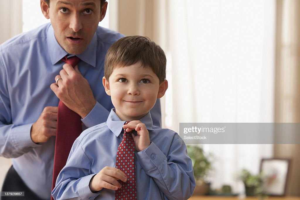 Father and son fixing ties together : Stock Photo