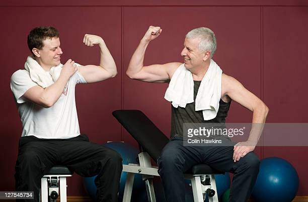 Father and son flexing muscles in gym