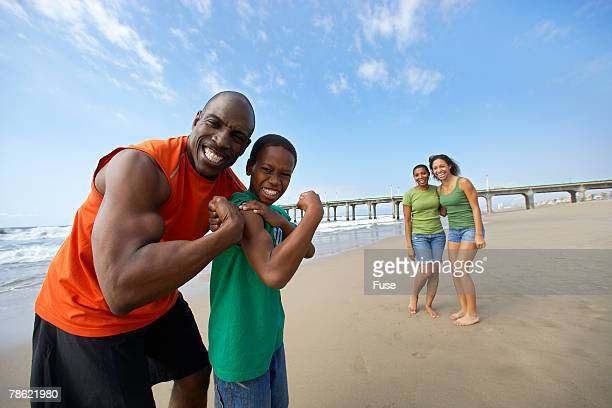 father and son flexing muscles on beach - flexing muscles stock pictures, royalty-free photos & images