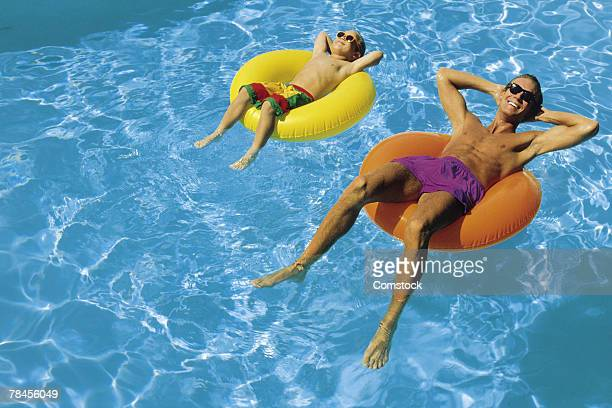 Father and son floating in swimming pool