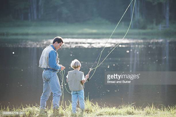 Father and son (8-10) fly fishing, rear view