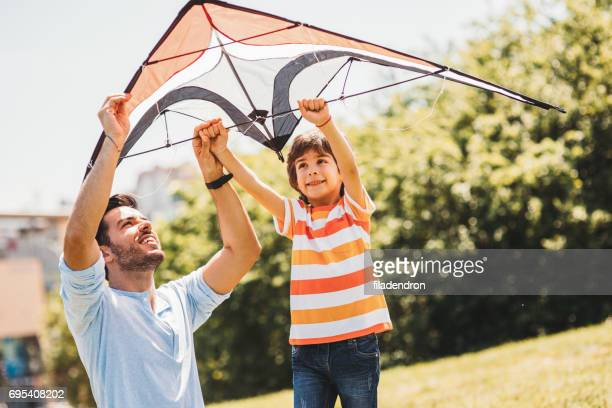 father and son flying a kite - kite toy stock photos and pictures