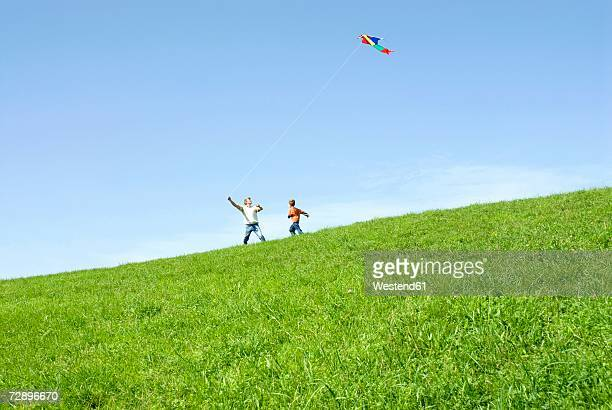 father and son (4-7) flying kite in park - kite toy stock pictures, royalty-free photos & images