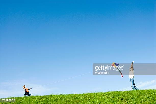 father and son (4-7) flying kite in park, side view - mid distance stock pictures, royalty-free photos & images