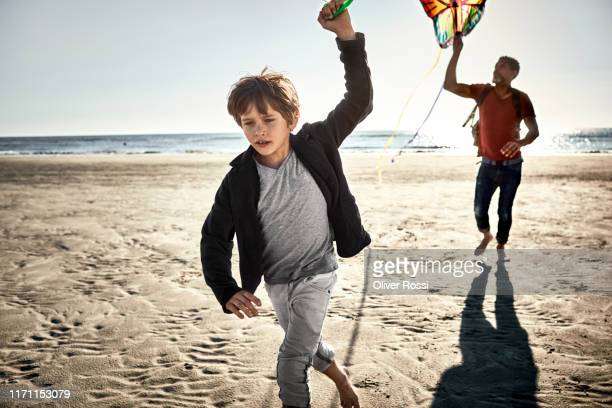 father and son flying kite on the beach - north sea stock pictures, royalty-free photos & images