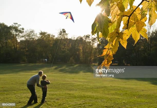 father and son flying kite - familie mit einem kind stock-fotos und bilder
