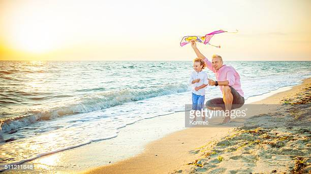 Father and son flying kites at the beach