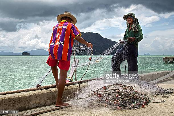 Father and son folding the fish net in Koh Yao Yai, Phang Nga, Thailand. Dramatic sky and beautiful background.