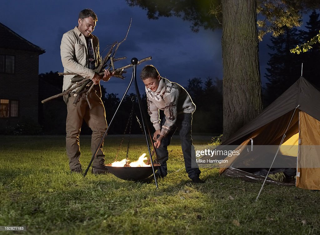 Father and son fuelling fire outside tent. : Foto de stock