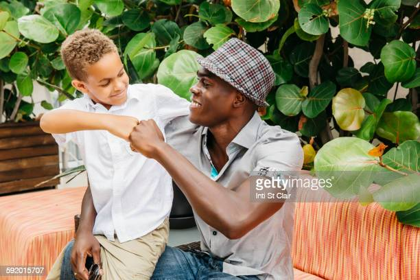 Father and son giving fist bump in backyard