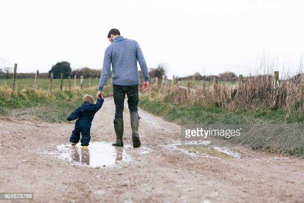 a father and son go for a walk along a muddy lane - sunday stock pictures, royalty-free photos & images
