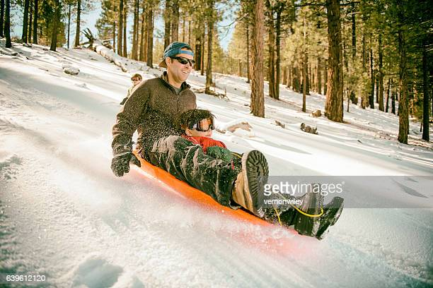 Father and son going fast down a hill