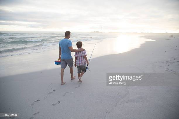 Father and son going fishing on a beach