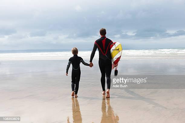father and son going surfing - traje de mergulho - fotografias e filmes do acervo