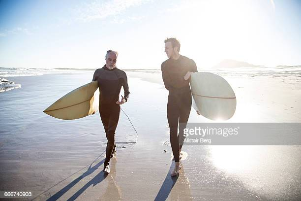 father and son going surfing together - leisure equipment stock pictures, royalty-free photos & images