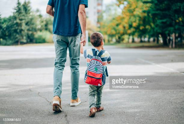 father and son going to kindergarten. - preschool child stock pictures, royalty-free photos & images