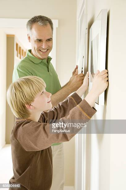 Father and son hanging pictures together in home