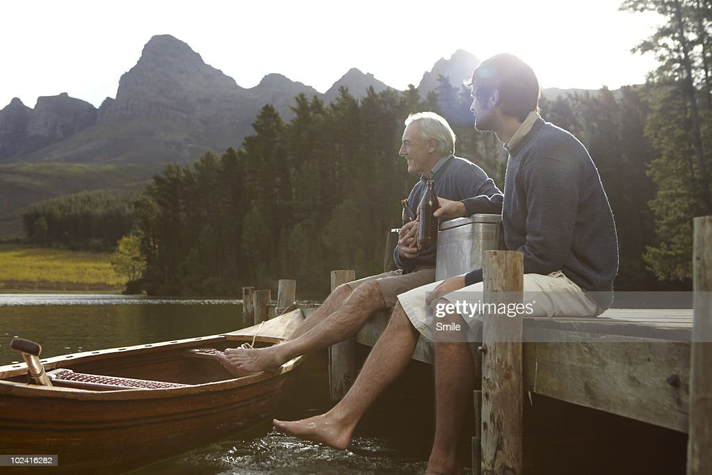 Father and son having a beer on jetty : Stock Photo