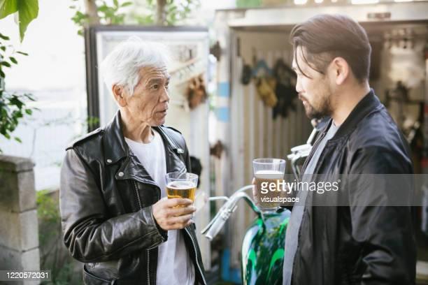 一緒にビールを飲む父と息子 - レザージャケット ストックフォトと画像