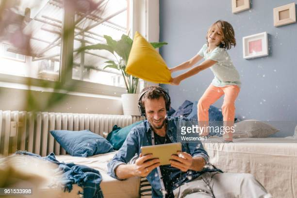 father and son having a pillow fight at home - huiselijk leven stockfoto's en -beelden