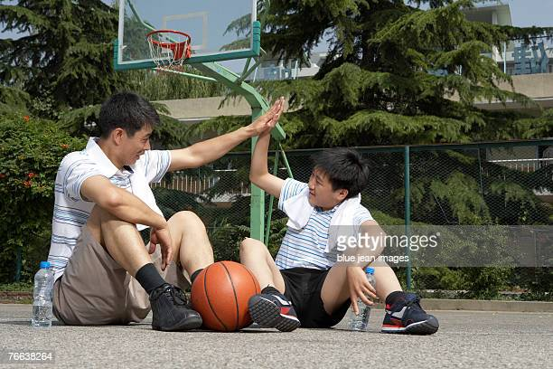Father and son having a rest on basketball court.