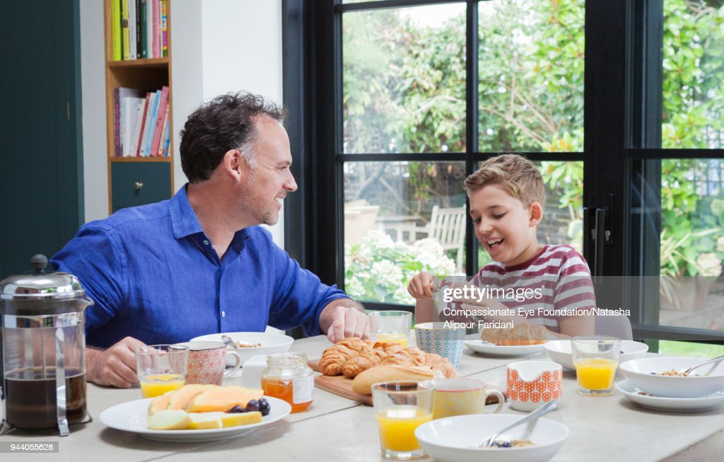Father and son having breakfast at dining table : Stock Photo