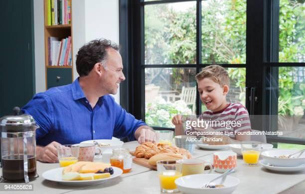 father and son having breakfast at dining table - atividades de fins de semana - fotografias e filmes do acervo