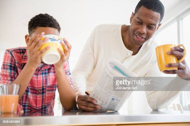 Father and son having breakfast in kitchen