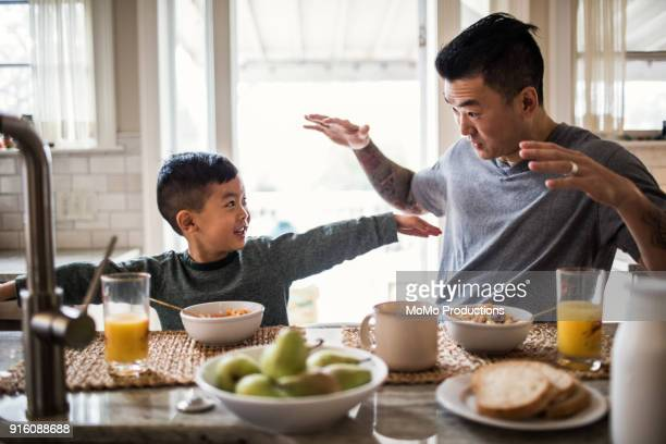father and son having breakfast in kitchen - asian and indian ethnicities stock pictures, royalty-free photos & images