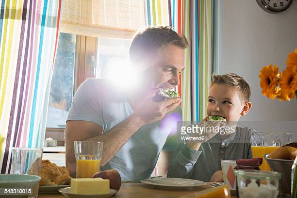 father and son having breakfast together - 口を使う ストックフォトと画像