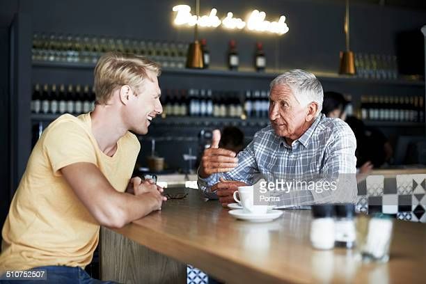 Father and son having coffee at cafe